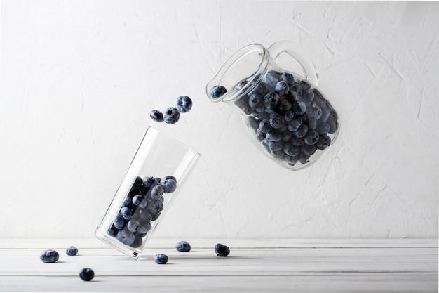 블루베리 부상. 용기의 블루베리를 흰색 배경에 있는 유리 비커에 붓습니다. 베리 스무디 만들기. 추상 창조적인 개념입니다.