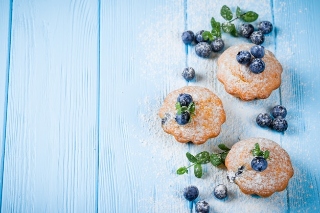 Blueberry muffin. homemade baked cupcake with blueberries, fresh berries, mint on wooden background.