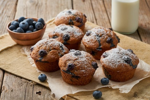 Blueberry muffin, side view. cupcakes with berries on old linen napkin, rustic wooden table