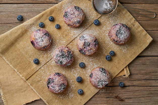 Blueberry muffin, top view. cupcakes with berries on old rustic linen napkin, wooden table