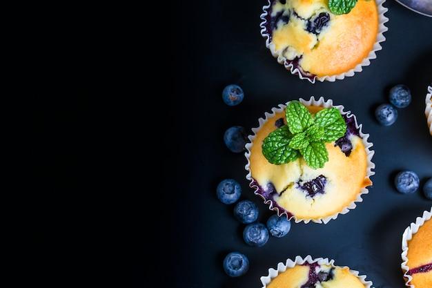 가루 설탕과 신선한 딸기와 블루 베리 머핀