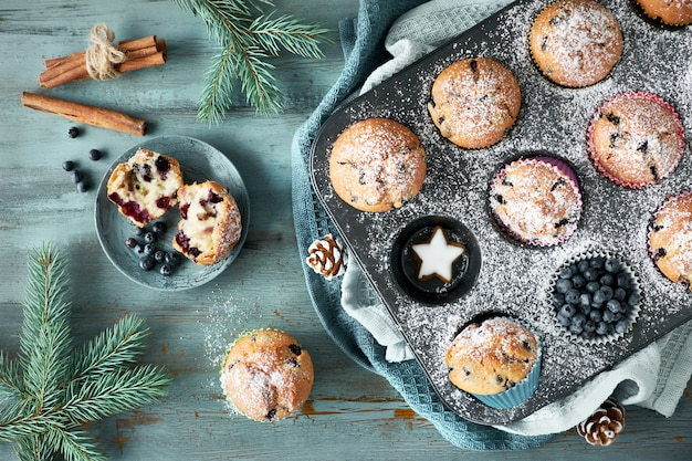 Blueberry muffins with sugar icing in a baking tray with christmas decorations around, top view