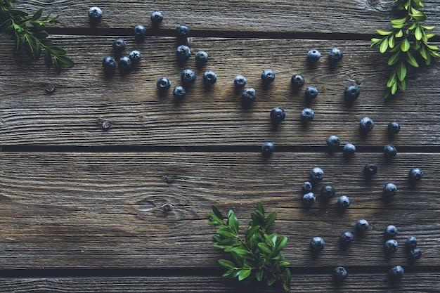 Черника на предпосылке деревянного стола. черника заделывают. здоровое питание, здоровье