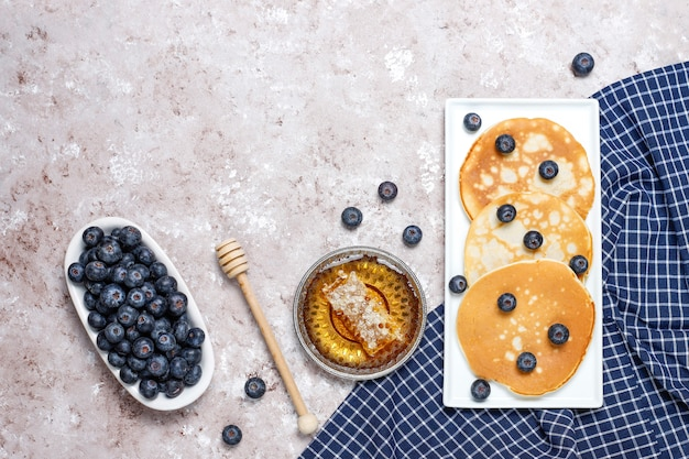 Blueberry pancakes on brown light surface