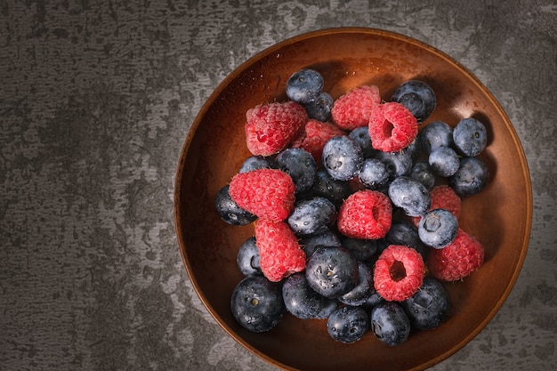 Blueberry and raspberry in a clay plate. raw berries mix close up. summer fresh berries.