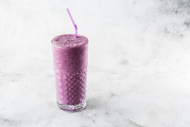 Blueberry smoothie or black currant purple milkshake in glass on bright marble background. overhead view, copy space. advertising for milkshake cafe menu. coffee shop menu. horizontal photo.