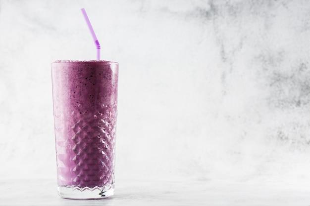 Blueberry smoothie or black currant purple milkshake in glass on bright marble background. overhead view, copy space. advertising for milkshake cafe menu. coffee shop menu. horizontal photo.