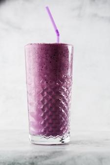 Blueberry smoothie or black currant purple milkshake in glass on bright marble background. overhead view, copy space. advertising for milkshake cafe menu. coffee shop menu. vertical photo.