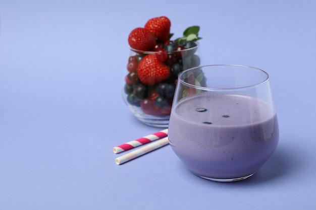 Черничный смузи, ингредиенты и соломка на фиолетовом фоне