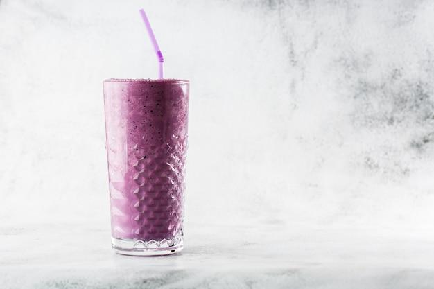 明るい大理石の背景にガラスのブルーベリーのスムージーや黒スグリの紫ミルクセーキ。俯瞰、コピースペース。ミルクセーキカフェメニューの広告。コーヒーショップメニュー。横の写真。