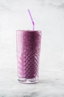 明るい大理石の背景にガラスのブルーベリーのスムージーや黒スグリの紫ミルクセーキ。俯瞰、コピースペース。ミルクセーキカフェメニューの広告。コーヒーショップメニュー。縦の写真。