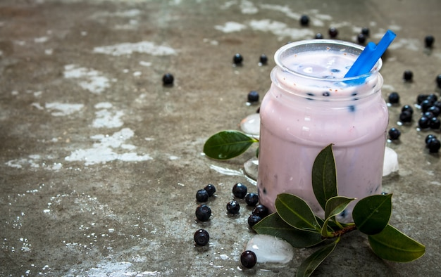 Blueberry smoothie with ice. on a stone background.