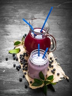 古い生地にブルーベリーのスムージーとフレッシュジュース。黒い木製のテーブルの上。