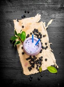 古い生地にブルーベリーのスムージー。黒い木製のテーブルの上。