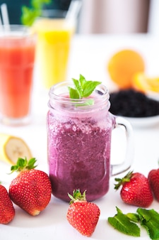 Blueberry smoothies on a white table with berries