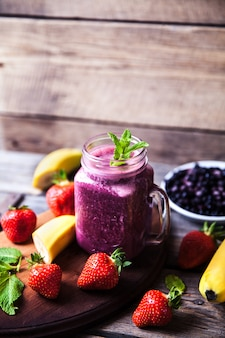 Blueberry smoothies on a wooden table with fruits. vitamins