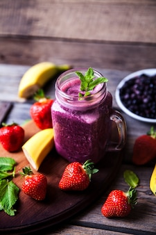 Blueberry smoothies on a wooden with fruits. vitamins a