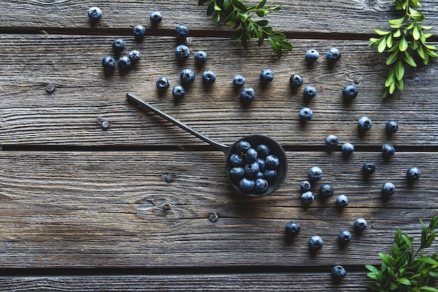 Blueberry in spoon on wooden table background.