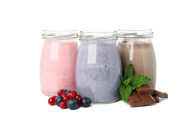 白い背景に分離されたブルーベリー、イチゴ、チョコレートのミルクセーキ