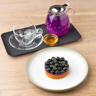 Черничный пирог и голубой чай гороховый цветок травяной чай. тайский голубой чай подается с медом и черничным пирогом на деревянном столе