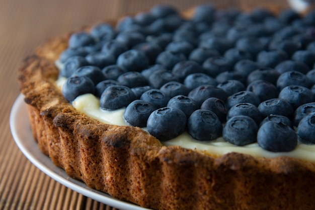 Blueberry tart or cake with cream and berries. homemade dessert, wooden board.