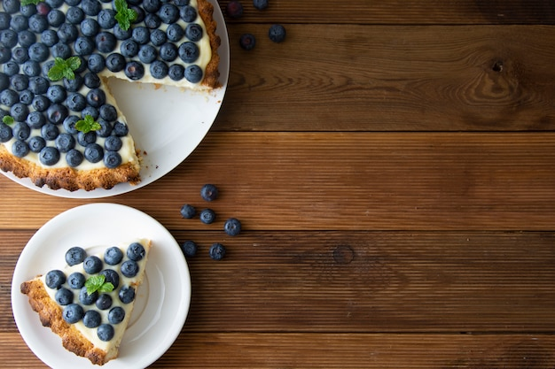 Blueberry tart or cake with cream and berries. homemade food, wooden, rustic background.