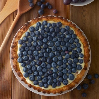 Blueberry tart or cake with cream and berries.