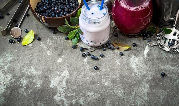 ブルーベリーのスムージーとジュースを添えたブルーベリー。石のテーブルの上。 Premium写真