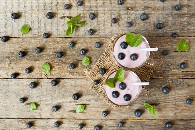 신선한 블루 베리와 나무 시골 풍 테이블에 민트와 유리 컵에 블루 베리 요구르트