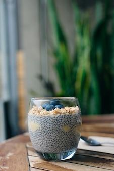白い木製のテーブルの上のグラスにグラノーラ、オート麦、チアシードを入れたブルーベリー ヨーグルト パフェ。健康的な朝食。閉じる