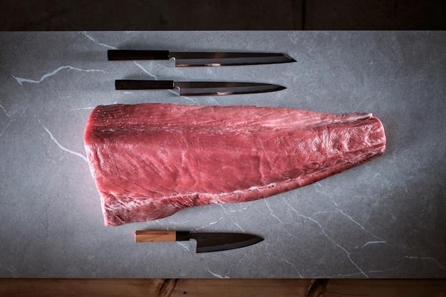 Корейка синего тунца на цементном фоне с тремя ножами