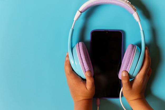 Bluelの背景に現代のスマートフォンとヘッドフォンを保持している子供の手。ガジェットの同期、相互作用。上面図、聞く音楽、ヘッドフォン、最新テクノロジー
