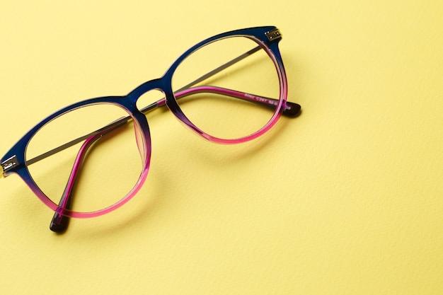 黄色の背景にブルーピンクのメガネ