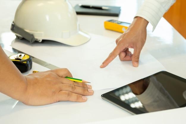 Азиатский архитектор работает над планом руки, указывая на эскиз bluepring.