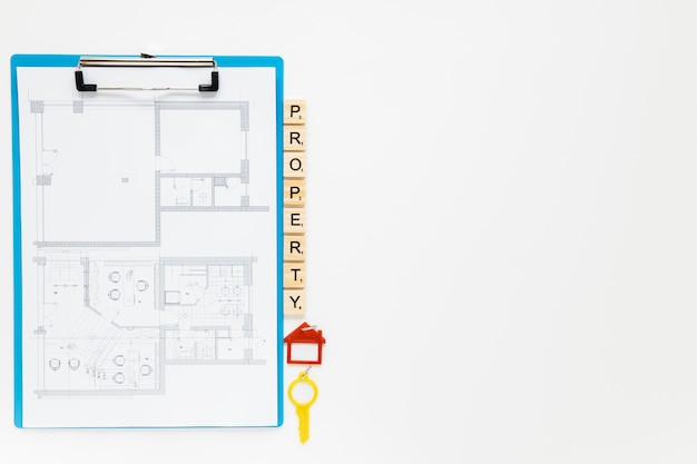 Blueprint clipboard with property blocks and house key on white backdrop