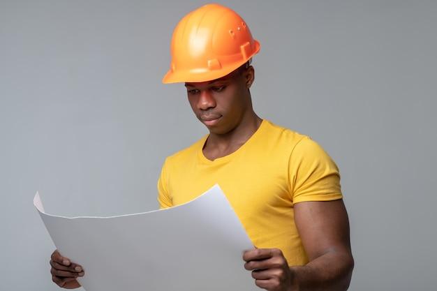 Чертеж чертежа. серьезный внимательный темнокожий молодой человек в шлеме рассматривает чертеж чертежа, держа в руках