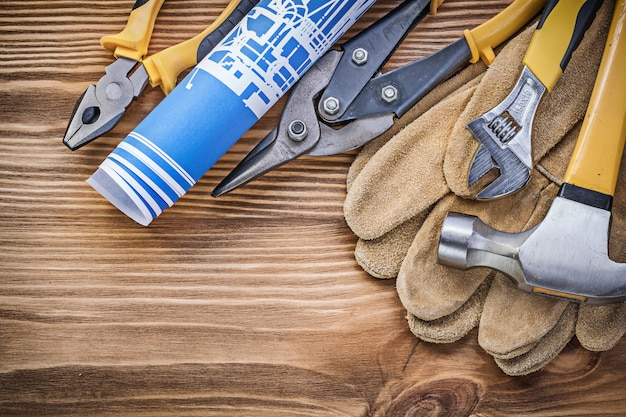 Blueprint safety gloves claw hammer gripping tongs tin snips adjustable wrench on wooden board