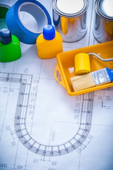 Blueprint with paint brush tray roller cans bottles and adhesive duct tapes construction concept