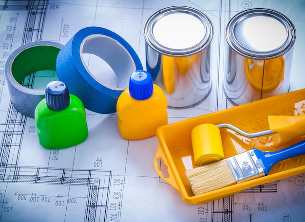 Blueprint with paint brush tray roller cans bottles and household tapes close up image construction concept