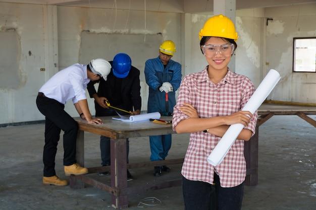 Женщина, как форман носить желтый хардхат холдинг blueprint постоянный