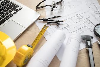 Blueprints and tools near laptop