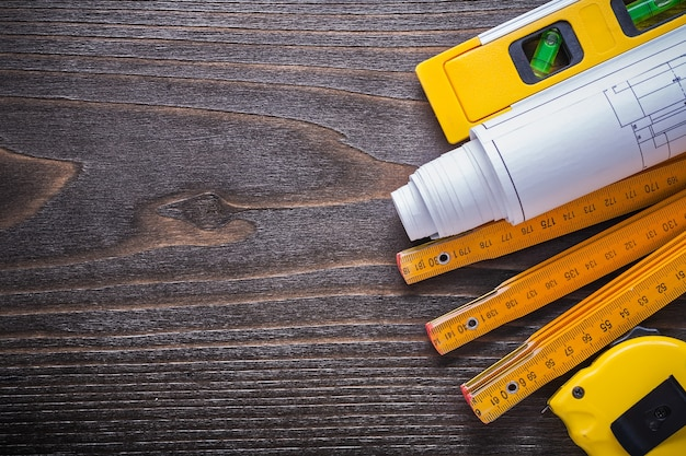 ヴィンテージの木製ボードのメンテナンスコンセプトに関する青写真の建設レベルの巻尺と木製のメーター。 Premium写真