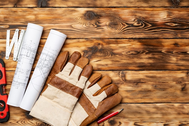 청사진, 수준 및 나무 테이블에 건설 노동자의 장갑