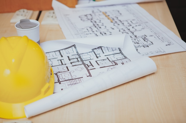 Blueprints and protective hardhat on the table