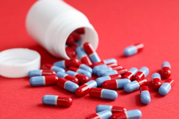 Синие медицинские таблетки, разбросанные из банки, лежат на красном фоне, концепция неконтролируемого употребления наркотиков