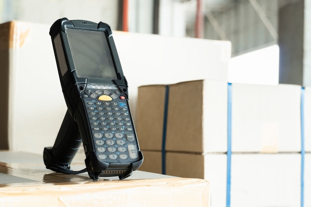 Bluetooth barcode scanner on shipment boxes, manufacturing cargo warehouse export. computer equipment for inventory management.