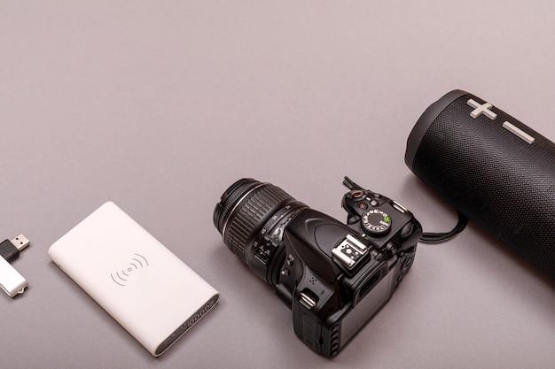 デジタル一眼レフカメラのクローズアップとbluetoothスピーカーとパワーバンク。オンライン音楽のコンセプト。