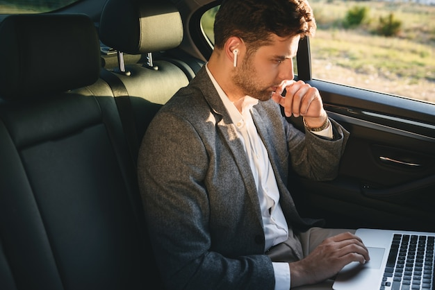 Успешный человек в костюме и наушниках bluetooth работает на ноутбуке, сидя на заднем сиденье в автомобиле бизнес класса