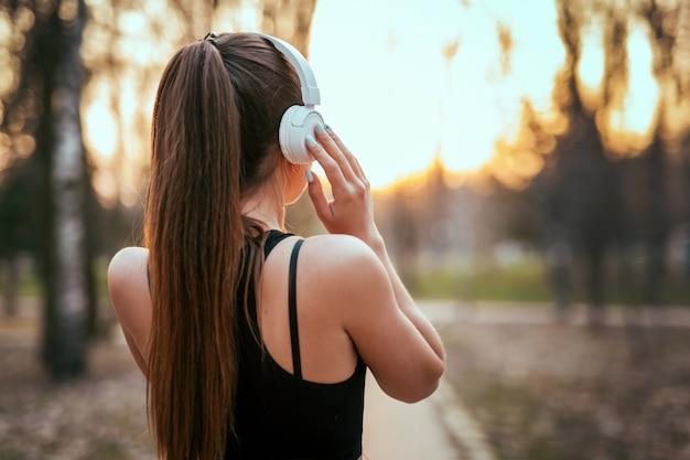 髪型の美しい女性がbluetoothヘッドフォンで背中と立って、遠くを見て、公園で日没で音楽を聴く