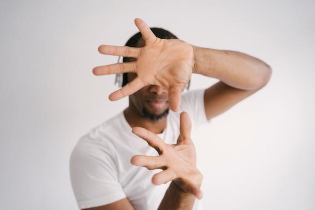 民族の人々と音楽のコンセプト。リズムアンドブルース。 bluetoothヘッドフォンで音楽を聴く魅力的なアフリカ系アメリカ人。